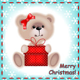 Teddy  bear girl with a Christmas gif. Christmas card. teddy  bear girl with a Christmas gift on the blue background with snowflakes Stock Photos