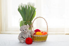 Teddy bear-girl sitting on a background of a bouquet of white tu Royalty Free Stock Photo