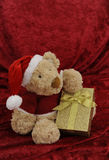 Teddy bear with golden gift box on red Royalty Free Stock Image