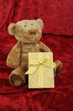 Teddy bear with golden gift box on red Royalty Free Stock Images