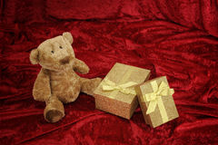 Teddy bear with golden gift box on red Stock Image