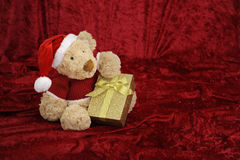 Teddy bear with golden gift box on red Stock Photos