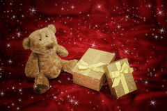 Teddy bear with golden gift box on red Stock Images
