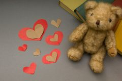 Teddy bear on a gray background, a red heart royalty free stock image