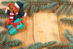 Teddy bear with green gift for Christmas and spruce branches, copy space for text Stock Images