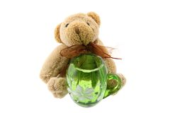 Teddy bear with a green jug isolated on white Stock Photos