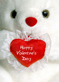 Teddy Bear Greeting. White teddy bear holding a heart shaped pillow that reads Happy Valentine's Day Royalty Free Stock Image
