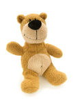Teddy bear greets. Brown teddy bear sitting with raised hand isolated over white Royalty Free Stock Images