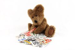 Teddy Bear With Grocery Coupons. A fuzzy little teddy bear sorting money saving grocery coupons Royalty Free Stock Images