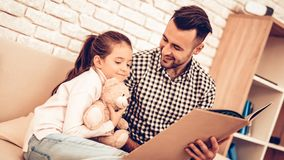 Teddy Bear in Hand. Father and Daughter on Sofa. Spend Time Together. Father`s day. Man Play with Girl. White Interior. Girl wiht. Man on Sofa. Play with Father royalty free stock images