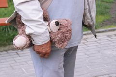 A teddy bear in the hand of a man. old person walk on the street. Grandpa holds a toy of a grandson or granddaughter`s child Stock Image