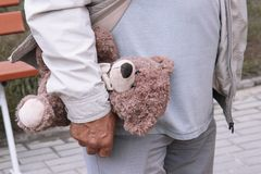 A teddy bear in the hand of a man. old person walk on the street. Grandpa holds a toy of a grandson or granddaughter`s child Royalty Free Stock Photo