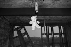 Teddy Bear Hanging In Derelict övergav Fie Station Building In Black & vit royaltyfri fotografi