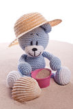 Teddy bear with hat on the beach Stock Photos