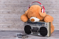 Teddy Bear with headphones listening music on Retro radio-cassette player.Vintage style. Retro radio-cassette player.Vintage style stock image