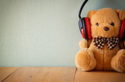 Teddy bear with headphones over wooden table Royalty Free Stock Photo