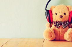 Teddy bear with headphones over wooden table Stock Image