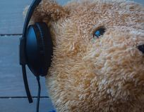 A teddy bear in the headphones on wooden background Royalty Free Stock Images