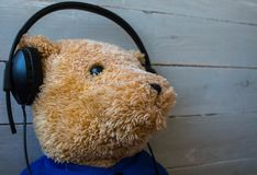 A teddy bear in the headphones on wooden background Stock Photo
