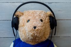 A teddy bear in the headphones on wooden background Stock Images
