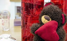 Teddy bear with a heart on a background of glass red bottles stock photo