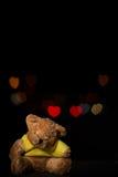 Teddy bear with heart bokeh on black background Stock Photos