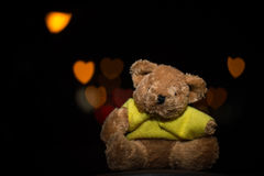 Teddy bear with heart bokeh on black background Stock Photo