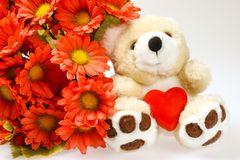 Teddy bear with heart and flowers stock photo