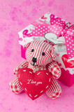 Teddy bear with a heart in the hands near a gift box and bokeh Royalty Free Stock Photos