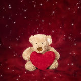 Teddy bear with heart shaped pillow on red Royalty Free Stock Photography
