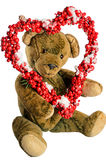 Teddy Bear with heart-shaped wreath of red berries as a greeting. For Valentine's Day Royalty Free Stock Photography