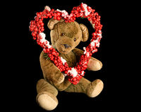 Teddy Bear with heart-shaped wreath of red berries as a greeting Stock Photos