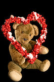 Teddy Bear with heart-shaped wreath of red berries as a greeting. For Valentine's Day Stock Photos