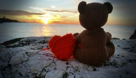 Teddy bear with heart to sunrise Stock Image