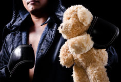 Teddy bear held by boxer. Close-up teddy bear held by boxer Royalty Free Stock Images