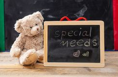 Teddy bear hiding behind a blackboard. Special needs text drawing on the blackboard. Special needs at school. Teddy bear hiding behind a blackboard. Special stock images