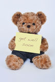 Teddy bear holding a  yellow sign saying Get Well Soon isolated on white background Royalty Free Stock Images
