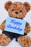 Teddy bear holding  blue sign saying Happy Birthday Royalty Free Stock Image