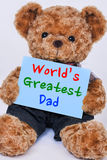 Teddy bear holding  blue sign saying World`s Greatest Dad Royalty Free Stock Photo