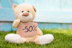 Teddy bear holding cardboard with information -50% stock image
