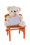 Teddy bear holding clear card on brown chair with white background. Stock Photo