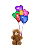 Teddy bear holding colorful heart shaped balloons.