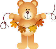 Teddy bear holding a garland of fall leaves Royalty Free Stock Photography