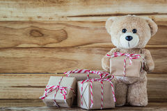 Teddy bear holding a gift box. A photo of teddy bear holding a gift box on plank wood board background Stock Photography