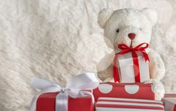 Teddy bear holding a gift tied with red ribbon. On wooden table, white wool background royalty free stock image