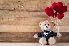 Teddy bear holding heart-shaped balloon Stock Image