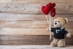 Teddy bear holding heart-shaped balloon Royalty Free Stock Images