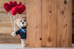 Teddy bear holding heart-shaped balloon Stock Photo