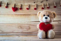 Teddy bear holding a heart-shaped pillow Stock Image