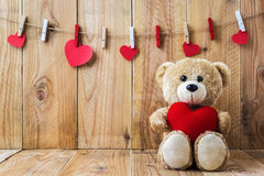 Teddy bear holding a heart-shaped pillow. A photo of Teddy bear holding a heart-shaped pillow on plank wood board with wood board background Stock Photography